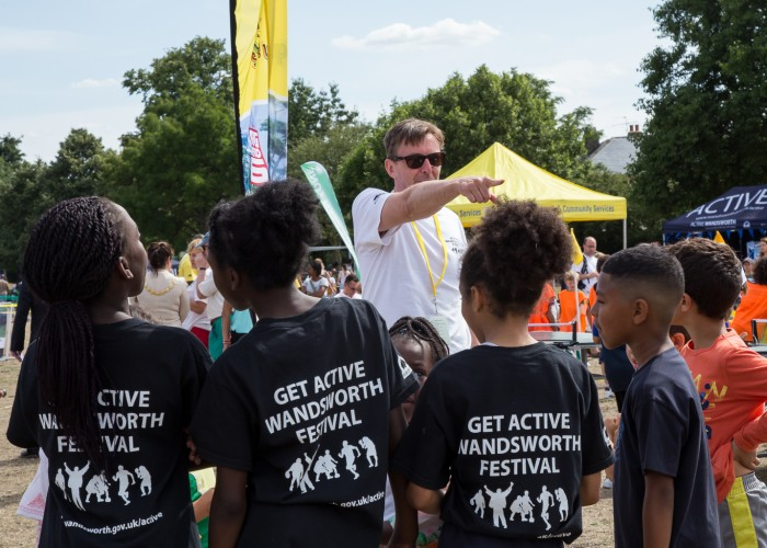 'a volunteer guides introduces children to a new sport'