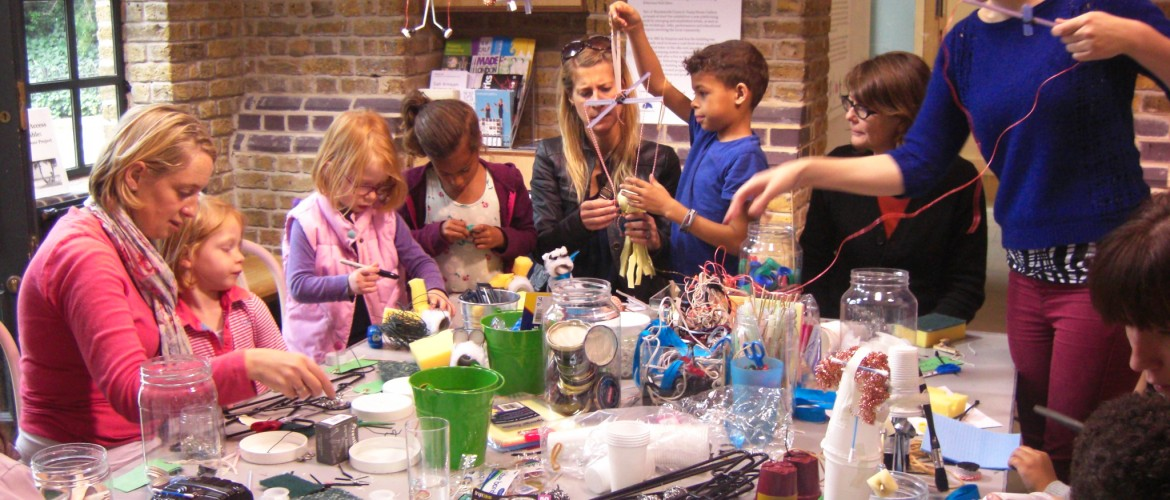 Image of group of children and parents participating in an art workshop.